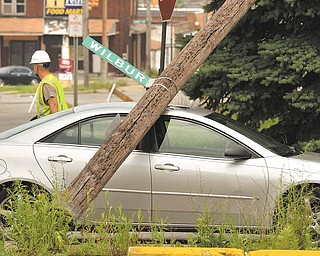 A utility pole pinned a car when a Youngstown Street Department truck brought down three utility poles after snagging onto power lines. The incident, which occurred about 10:30 a.m. Monday at Wilbur Street and South Avenue on the South Side, closed the intersection for several hours.