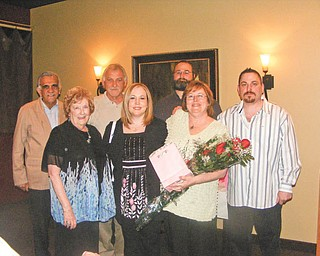 Cathy Pokrivnak, holding flowers, celebrates being named 2011 Woman of the Year by the Youngstown Charter Chapter of the American Business Women's Association. With her are, front left, Mary Ann Rushton, her mother; Susan Carosella, her daughter; and back, from left, stepdad Gus Merola, husband John Pokrivnak, son Steve Baytos IV and son-in-law Ed Carosella.