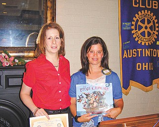 Learning about resources: Linda Titus, left, of the Ursuline Sisters HIV/AIDS Ministry, recently spoke to the Rotary Club of Austintown about services and resources offered by the Ursuline Sisters that help individuals or families dealing with HIV or AIDS. Deanna Spirko, right, incoming president of Austintown Rotary, presents a certificate for a children's book to be donated in the Ursuline Sisters' name to Woodside Elementary Library in Austintown.