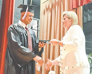 Donald Robinson, a keynote speaker at the Adult Basic and Literacy Education Program commencement ceremony, accepts his diploma from Denise Vaclav-Danko, ABLE director. The ceremony was Thursday at Chaney High School in Youngstown.