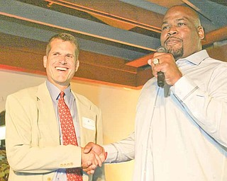San Francisco 49ers head coach Jim Harbaugh, left, is introduced by former 49ers player Steve Wallace during the DeBartolo Scholarship banquet Monday at Leo's Ristorante in Howland.
