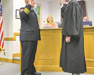 Don Hutchison, left, is sworn in by Judge Scott Hunter as the new chief of Cardinal Joint Fire District, which serves the city of Canfield and Canfield Township. Hutchison joined the district in 1989 and worked with former Chief Robert J. Tieche until Tieche's death in May. The ceremony was Monday.