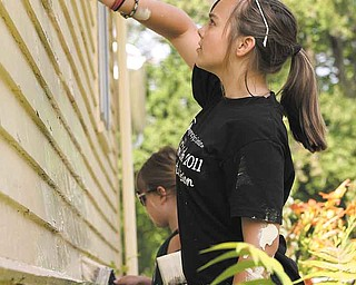 Michala Sakofas, 12, youth mission member of Tabernacle Evangelical Presbyterian Church, helps paint the rear of the house at 762 W. LaClede Ave. on Youngstown's South Sid