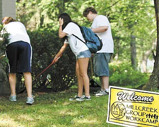 Volunteers from Millcreek Youth Workcamp, from left, Emily Lado, 16, of Orwigsburg, Pa.; Hosanna Kim, 16, of Chappaqua, N.Y.; and Jeremy Schmidt, 16, of Itasca, Ill., help clean up the yard at a home in the 500 block of West Laclede Avenue.