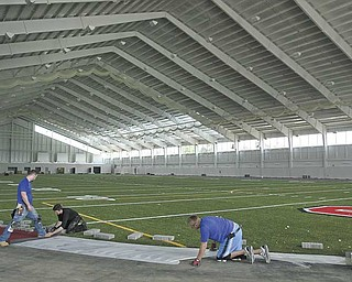 Workers install the indoor track at Youngstown State University's $10 million Watson and Tressel Training Site.  Most of the work is completed, and the official unveiling should take place in the next few weeks. The university hopes the 125,000-square-foot state-of-the art facility will act as a recruiting tool.