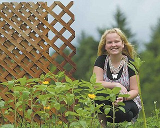 Tori Snyder, 17, one of the students in Kathleen Kromer's Columbiana Educational Service Center class, is all smiles as she surveys sunflowers blooming in the Bloomin' Butterfly Garden shaped like a butterfly at Goodness Grows ministry at Common Ground Church Community in Beaver Township. She wears a butterfly necklace to go with the garden theme. The garden features plants to attract birds, butterflies and bees.