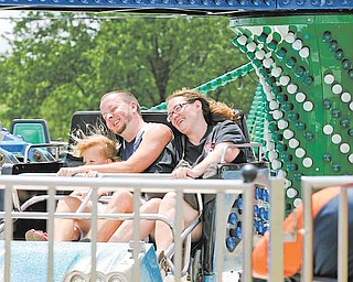 Tom and Shannon Semple of Liberty ride the Twister with their 5-year-old daughter, Mia. The fair runs through Monday.