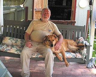 "Jerry Hoover of Boardman is relaxing with his ""granddog,"" Bullseye, who was adopted from Mahoning County Dog Pound."