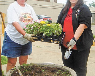 Beautification project: Roberta Lawrentz, left, and Sue Ellen Davis of Girard Junior Women's Club fill a planter in downtown Girard. The annual project was initiated by Davis's mother, Jane Harris. Planters in front of businesses are filled with flowers every summer as one of the group's projects. Girard Junior Women are dedicated to serving the Girard community and most recently donated to Emmanuel House and presented a Girard graduate with scholarship money. Anyone interested in joining should contact Lawrentz or any member of GJWC.
