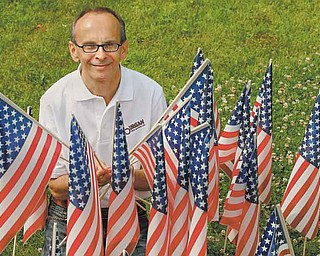 American flags surround Rich Suhovecky, who embraced a flag-planting project started by co-worker Karen Ament at Burgan Real Estate. Suhovecky coordinates the placement of 3,000 small U.S. flags at homes throughout Hubbard in the days leading up to July Fourth. He said he does it because he loves America and Hubbard.