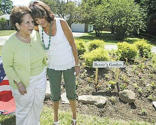 Bessie Anderson, left, is congratulated by Jodi Stoyak, Liberty Township trustee, during a dedication ceremony Friday at Anderson's garden on Logan Way in Liberty. Anderson, a master gardener in Trumbull County, has created several gardens in the township over the past decade.