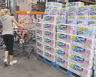 In this June 13, 2011 photo, shoppers buy toilet paper at Costco in Mountain View, Calif. Shoppers go into Costco, TJ Maxx or a DSW shoe store looking for a bargain on something they need and end up splurging on irresistible finds.(AP Photo/Paul Sakuma)
