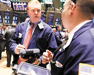 FILE - In this June 22, 2011 file photo, Terence Toal, left, talks to a fellow trader as they work on the floor of the New York Stock Exchange. Global stock markets pushed modestly higher Tuesday, July 5, as investors awaited a raft of U.S. economic data this week that culminates with closely-watched payrolls figures.(AP Photo/Richard Drew, file)