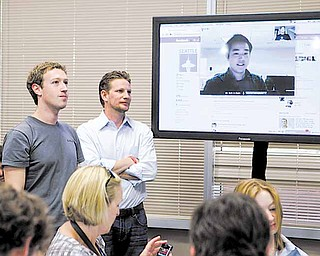 Facebook CEO Mark Zuckerberg, left, watches a demonstration of Video Chat during an announcement at Facebook headquarters in Palo Alto, Calif., Wednesday, July 6, 2011. (AP Photo/Paul Sakuma)