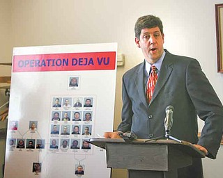 U.S. Attorney Steven M. Dettelbach stands near a poster of the 25 people wanted in a federal investigation into heroin sales in Youngstown. At a news conference Wednesday, he discussed federal and local law enforcement's determination to press forward with aggressive pursuit of those distributing drugs and illegally carrying guns in the area.