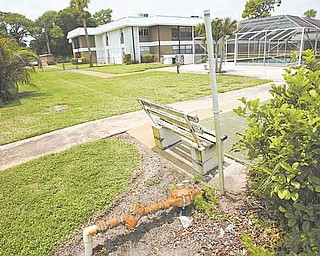 In this June 15, 2011 photo, an empty park bench and rusting pipe sit near the swimming pool at the Inlet House, in Fort Pierce, Fla. The complex was an affordable place that the 55-and-older set aspired to. But now the Homeowner's association has levied a $6,000 assessment on every homeowner and then foreclosed on seniors who did not owe the bank a dime but could not afford the association bill. (AP Photo/J Pat Carter)