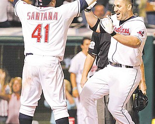 Cleveland Indians' Travis Hafner, right, is greeted at home by teammate Carlos Santana (41) after hitting a walk-off grand slam off Toronto Blue Jays' reliever Luis Perez in the bottom of the ninth inning of a baseball game, Thursday, July 7, 2011, in Cleveland. The Indians won the game 5-4. (AP Photo/Amy Sancetta)