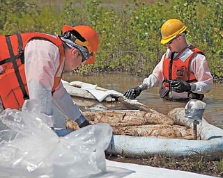 Cleanup workers use oil-absorbent materials alongside the Yellowstone River in Laurel, Mont. An Exxon