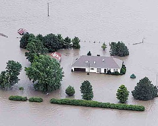 FILE - In this June 13, 2011 file photo, a home is engulfed by flood water in Hamburg, Iowa from the rising Missouri River. Insurance agents in states along the swollen Missouri River basin say federal officials are causing widespread confusion among property owners by pushing the sale of flood insurance policies that might not cover damage from the river flooding.  (AP Photo/Nati Harnik, File)