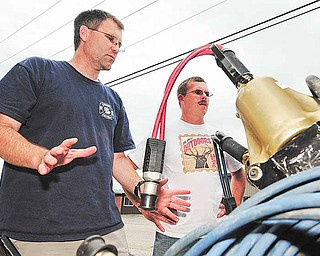 In a July 5, 2011 photo, Brent Anderson, left, and Ken Rackow, both of Goodview, Minn., make safety inspections on the Goodview Fire Department's engine #2. Both Anderson and Rackow were recently laid off from their jobs at Whitewater State Park and have been upping the amount of time they spend volunteering at the Goodview Fire Department because of it. (AP Photo/Winona Daily News, Rory O'Driscoll)