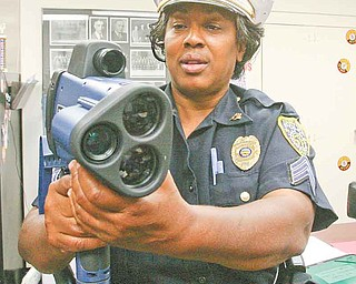 Youngstown Police Detective Sgt. Anita Davis demonstrates the laser radar gun with camera and video that Youngstown police plan to train residents to use. Police Chief Jimmy Hughes argues the new program will be more eff ective than placing warning signs about speeding in city neighborhoods.