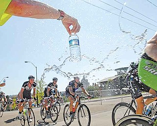 Volunteers pass bottles of water to racers during the men's Criterium on the final day of the 2011 Tour of the Valley on Sunday afternoon. More than 340 cyclists took part in the event.