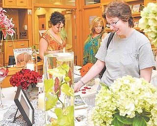 Bride-to-be Emily Smith of Warren, foreground, and Sarah Hahn, left, with mom, Barbara, view samples of flower arrangements from A Floral Aff air at the 2011 Bridal Fair at the D.D. and Velma Davis Education and Visitor Center at Fellows Riverside Gardens, Mill Creek MetroParks, Youngstown.