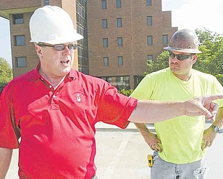 Danny O'Connell, director of support services at Youngstown State University, left, and Ron Williams of Suburban Construction of Cleveland look over the work Monday at the parking deck on Lincoln Avenue on campus. The project is on schedule.