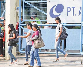 In this photo taken May 26, 2011, workers leave a factory that make Converse shoes, in Gunung Putri, West java, Indonesia. Workers making Converse sneakers in Indonesia said supervisors throw shoes at them, slap them in the face and call them dogs and pigs. Nike, the brand's owner, admits that such abuses have occurred among the contractors that make its hip high-tops but claims there was little it could do to stop it. (AP Photo/Achmad Ibrahim)