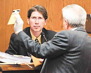 Prosecuting attorney Richard Bombik, right, holds up evidence for evidence investigator Curtiss Jones during the trial of Anthony Sowell Wednesday, July 13, 2011, in Cleveland.  Sowell, charged with killing 11 women, has has pleaded not guilty. He could face the death penalty if convicted. (AP Photo/Marvin Fong, Pool)