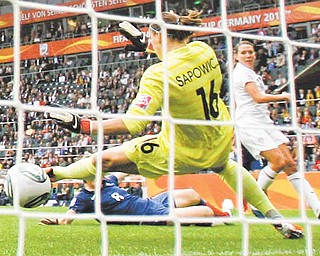United States' Lauren Cheney scores the opening goal past France goalkeeper Celine Deville during the semifinal match between France and the United States at the Women's Soccer World Cup in Moenchengladbach, Germany, Wednesday, July 13, 2011. (AP Photo/Frank Augstein)