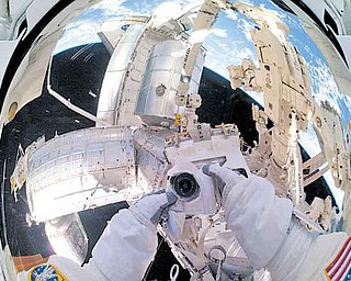 A panoramic view of the International Space Station, space shuttle Atlantis and Earth refl ected off of NASA astronaut Mike Fossum's helmet visor during a spacewalk July 12. The Robotic Refueling Mission can be seen just above Fossum's hands.