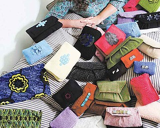 In this photo taken June 16, 2011, Sinead Fyda poses with purses created by Tanzanian women in Hilliard, Ohio.  Fyda lives in Tanzania up to eight months at a time while developing Jishike Social Couture, a business in which 21 women — many of them mothers of her former students — create handmade purses and bags that she sells when back in Columbus. (AP Photo/The Columbus Dispatch, Eric Albrecht)