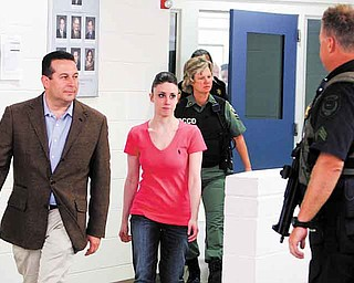 Casey Anthony, center, walks out of the Orange County Jail with her attorney Jose Baez, left,  during her release in Orlando, Fla., early Sunday, July 17, 2011.  Anthony was acquitted last week of murder in the death of her daughter, Caylee. (AP Photo/Red Huber, Pool)