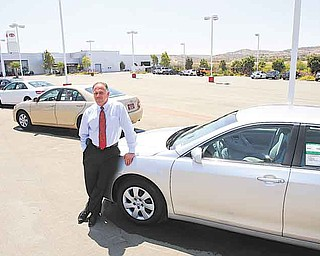 In this July 11, 2011 photo, Wayne B. Meyer, President of Sunroad Automotive in San Diego, leans on a car at his Chula Vista, Calif. dealership where a diminished inventory for small cars is evident in his near empty lot. (AP Photo/Lenny Ignelzi)