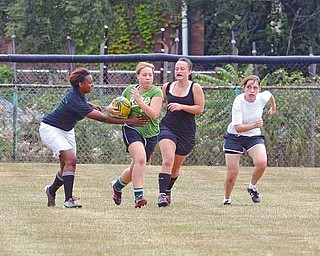 The Youngstown Rugby Club practices recently at Harrison Field. Jenni Nemes, second from left, runs with the ball, as Tim'Aira Gandy, left, Tiphanie Kalista, second from right, and Becky Coyne give chase.