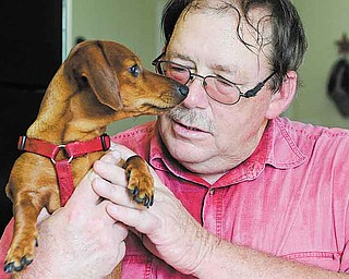 In this July 13, 2011 photo, Richard Smith poses for a photo with his dog Willie at his home in Vidor, Texas. Smith, who has multiple sclerosis and knee and ankle problems, once struggled to walk to his mailbox. Now, he walks three to four miles a day. He's dropped 40 pounds in two years, and his blood pressure and cholesterol have lowered.(AP Photo/Pat Sullivan)