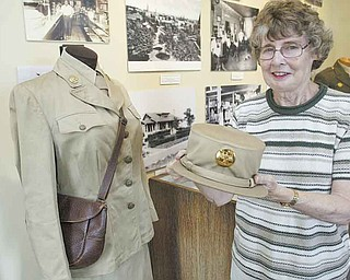 Carley O'Neill, librarian of Girard Historical Society, holds the hat worn by Ruth E. Rulli (1908-2008) of Girard, who served in the U.S. Army Air Corps, Boston Fighter Wing. Her uniform also is shown.