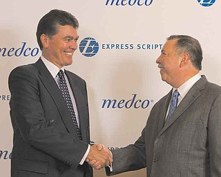 In this photo provided by Express Scripts, David Snow, CEO of Medco Health Solutions, left,  and George Paz, CEO of Express Scripts, shake hands Thursday July 21, 2011, after conclusion of negotiations to merge the two companies.  The new company will be known as Express Scripts with headquarters in St. Louis, Mo.  (AP Photo/Express Scripts, Karen Elshout)