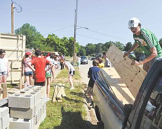 Michael Croft, 15, right, of Northern Ireland, moves lumber at the site of a Habitat for Humanity project at 1316 Dryden Ave. in Youngstown. Teens with the Mahoning Valley Ulster Project performed the community service Thursday.