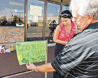 Forum Roller World owner Walt Hedrick and Julie Tam look at a sign left in front of the roller rink in Grand Prairie, Texas on Sunday, July 24, 2011, where police say a man gunned down four members of his estranged wife's family before fatally shooting himself at birthday party for his son Saturday night. (AP Photo/Richard W. Rodriguez)