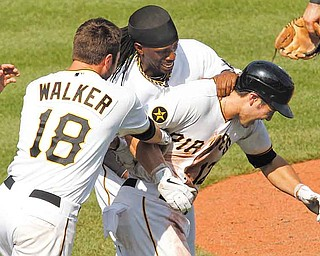 Pittsburgh Pirates' Chase d'Arnaud, right, celebrates with teammates Andrew McCutchen, center, and Neil Walker (18) after hitting a walkoff sacrifice fly to score the winning run in the tenth inning of a baseball game against the St. Louis Cardinals in Pittsburgh, Sunday, July 24, 2011. The Pirates won 4-3. (AP Photo/Gene J. Puskar)