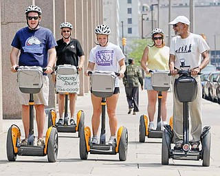 Karl C. Johnson, right, takes people on a tour of downtown Cleveland Monday, July 25, 2011. Sam Cregar, left to right front,  and Abby Moore,  are from Chagrin Falls, Ohio. (AP Photo/Tony Dejak)
