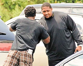 Pittsburgh Steelers running back Rashard Mendehall, left, greats offensive lineman Ramon Foster in the parking lot of the team's football training facility in Pittsburgh, Tuesday, July 26, 2011, the day after the NFL lockout ended.  (AP Photo/Gene J. Puskar)