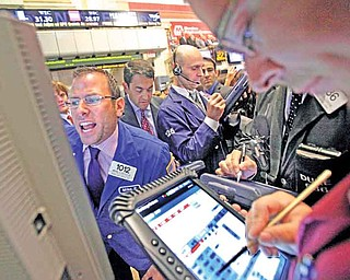 Specialist Michael Pistillo, left, calls out prices as he works at his post on the floor of the New York Stock Exchange Wednesday, July 27, 2011. (AP Photo/Richard Drew)