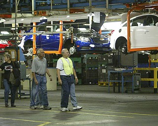 ROBERT  K.  YOSAY  | THE VINDICATOR --..as cars move over head people tour the GM facility..The Lordstown Complex is a General Motors automobile factory in Lordstown, Ohio comprising three facilities: Vehicle Assembly, Metal Center, and Paint Shop. The plant opened in 1966. Lordstown currently builds the global Chevrolet Cruze compact car.The plant welcomed over 9000 visitors to view the  Metal Center ( west plant) and the asembly plant on Thursday.--30-..(AP Photo/The Vindicator, Robert K. Yosay)