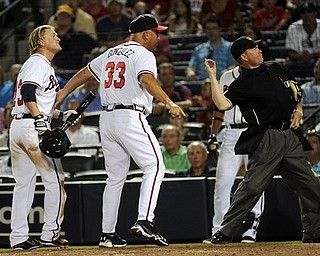 Atlanta Braves manager Fredi Gonzalez (33) is ejected by home plate umpire Jerry Meals after arguing the ejection of Nate McLouth, left, after McLouth argued a strike out during the ninth inning of a baseball game against the Pittsburgh Pirates, Tuesday, July 26, 2011. in Atlanta. (AP Photo/John Amis)