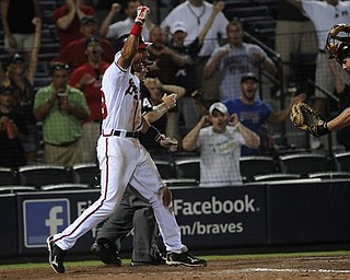 Atlanta Braves' Julio Lugo reacts to a safe call at home plate to end the game as Pittsburgh Pirates catcher Michael McKenry shows the umpire the ball during the 19th inning of a baseball game, early Wednesday, July 27, 2011. in Atlanta. Atlanta won 3-2. (AP Photo/John Amis)