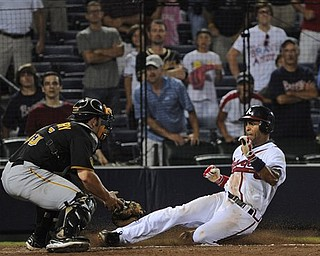 Atlanta Braves' Julio Lugo, right, slides into home plate safely to score the game-winning run as Pittsburgh Pirates catcher Michael McKenry tries to make the tag during the 19th inning of a baseball game, early Wednesday, July 27, 2011. in Atlanta. The Braves won 3-2. (AP Photo/John Amis)