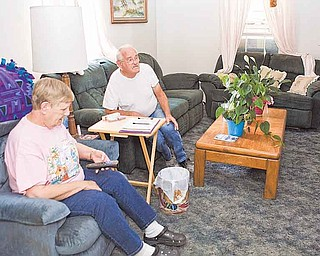 "In this July 22 photo, John Pangburn and his wife, Wanda, watch television in their home on a hot summer day in Mulhall, Okla. ""I can't take the heat like my husband can,"" said Wanda. ""I can go outside for a little bit, but I just don't stay out for long."""